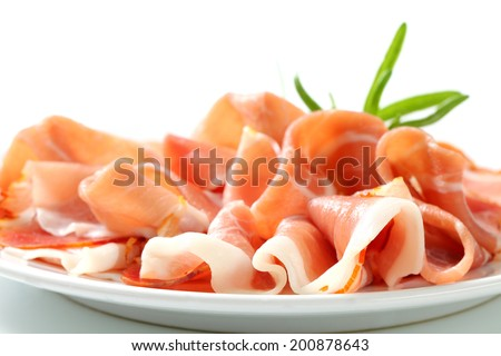 Slices of delicious prosciutto on a plate - stock photo