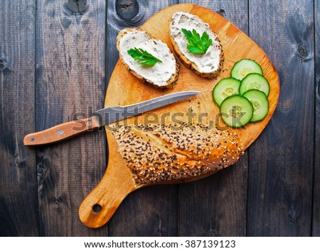 Slices of fresh cucumber, baguette with sesame, sandwich with cream cheese and parsley, knife on wooden cutting board - stock photo