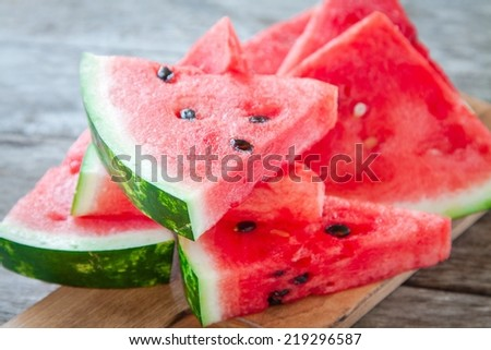 slices of fresh juicy organic watermelon on a wooden background - stock photo