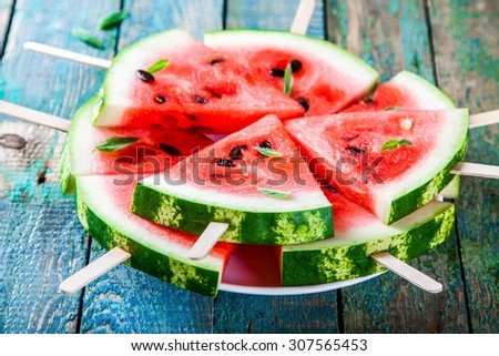 Slices of fresh juicy watermelon on plate closeup on rustic wooden table - stock photo