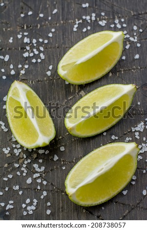 Slices of fresh lime and fleur de sel on a dark wood shabby surface - stock photo