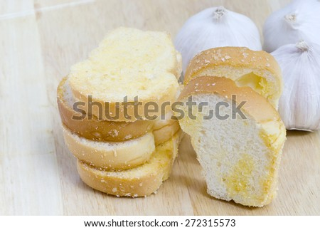 Slices of freshly baked garlic bread  with butter and sugar. Shallow dof. - stock photo