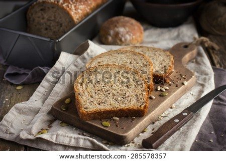slices of freshly baked  multigrain bread on rustic background - stock photo