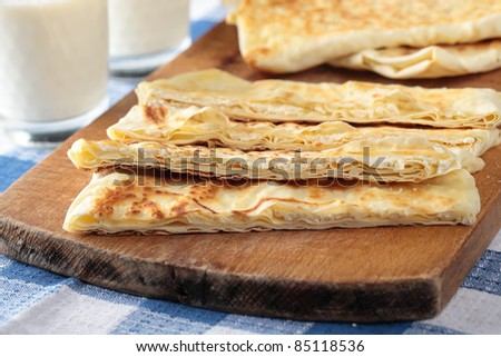 Slices of gozleme with cheese on a cutting board - stock photo