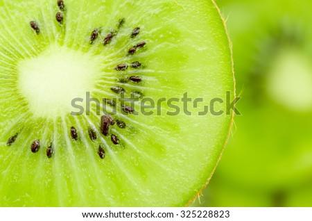 Slices of kiwi fruit on kiwi background. - stock photo