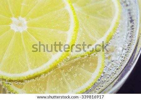 Slices of lemon? in soda water. Lime Cocktail. The liquid drink. Bubbles of carbon dioxide. The background texture. Tropical citrus fruit. Macro lemon?. Ingredient. - stock photo
