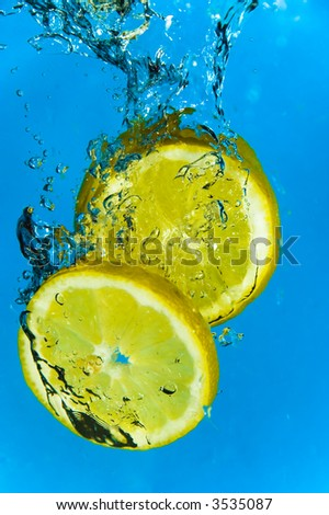 Slices of lemon plunging into icy water - stock photo