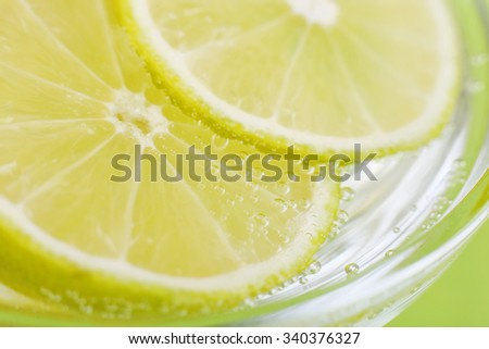 Slices of lime in soda water. Lime Cocktail. The liquid drink. Bubbles of carbon dioxide. The background texture. Tropical citrus fruit. Macro Lime. Ingredient. - stock photo