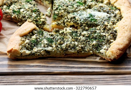 Slices of open pie with spinach on table close up - stock photo