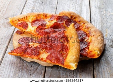 Slices of Pepperoni Pizza with Tomatoes Sauce and Cheese on Wooden Plate closeup on Rustic Wooden background - stock photo