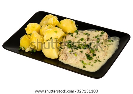 Slices of pork tenderloin with potatoes stewed in cream sauce - served on the black plate. isolated. - stock photo