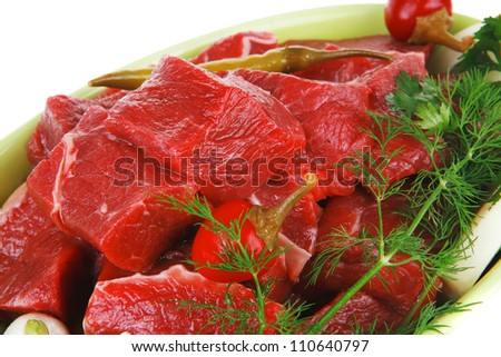 slices of raw fresh beef meat fillet in a ceramic dish with garlic and red peppers isolated over white background - stock photo