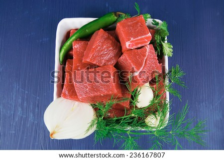 slices of raw fresh beef meat fillet in a white bowls with dill and green peppers serving over blue wooden table - stock photo