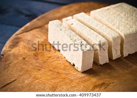 Slices of raw tofu on shabby beige cutting board - stock photo