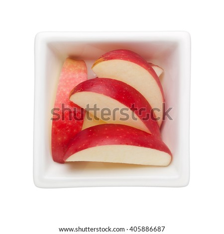 Slices of red apple in a square bowl isolated on white background - stock photo