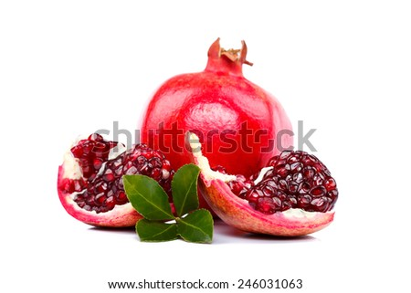 Slices of red pomegranate with green leaf isolated on white - stock photo