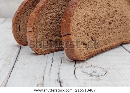 slices of rye bread on a wooden table - stock photo