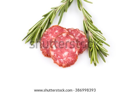 slices of salami isolated on a white background with rosemary - stock photo