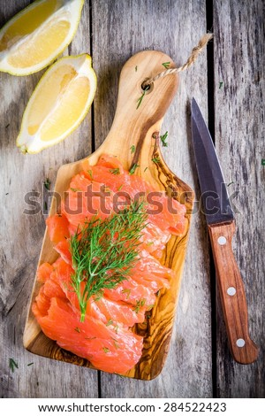 Slices of smoked salmon on a wooden chopping board with dill on rustic table - stock photo