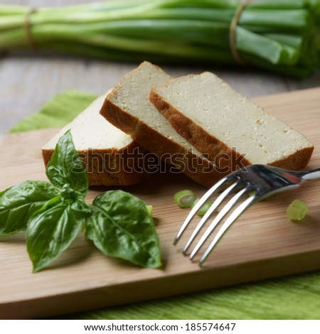 slices of smoked tofu with basil and green onions - stock photo