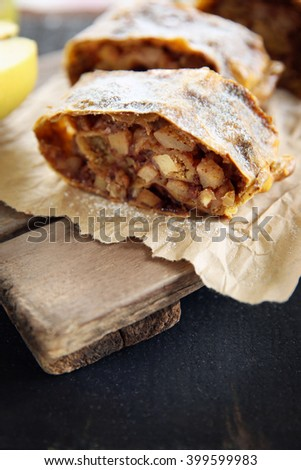 Slices of strudel with apples, walnut and raisins on parchment - stock photo