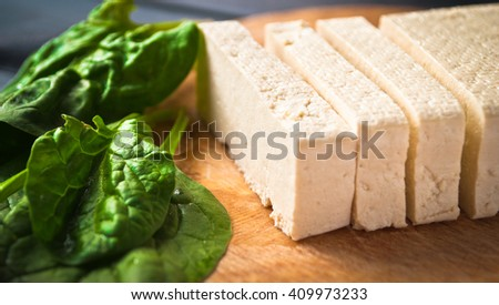 Slices of uncooked tofu and green leaves of fresh spinach on cutting board. Ingredients for vegetarian meal - stock photo