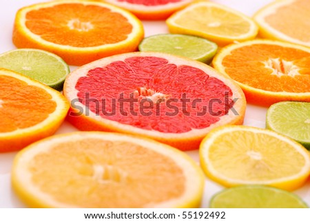 Slices of various citruses on white background - stock photo