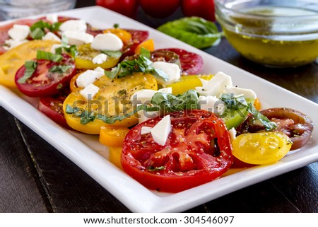 Slices of vine ripe heirloom tomato varieties with fresh basil, salt, pepper, olive oil and fresh herbs sitting on square white plate - stock photo