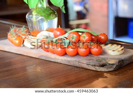 Slices of white toasted bread with a bunch of tomatoes - stock photo