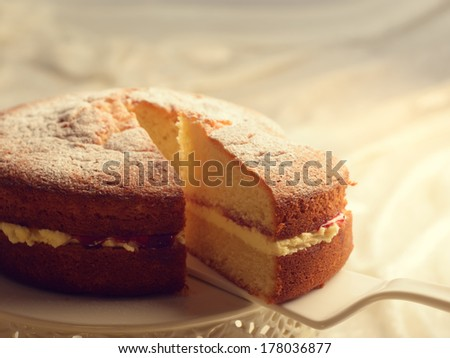 Slicing a Victoria sponge cake revealing the jam and buttercream filling - stock photo