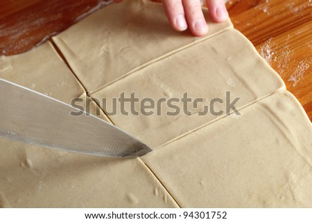 Slicing dough sheet - stock photo