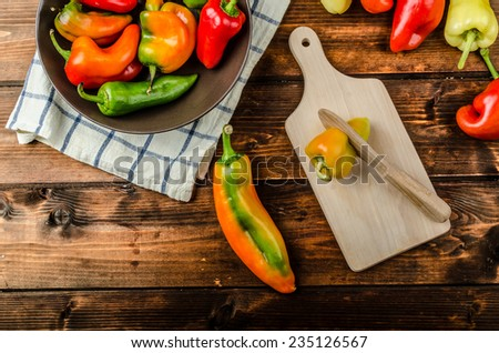 Slicing peppers with wood knife on wood board - stock photo