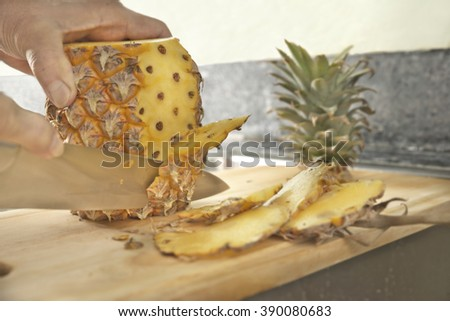 Slicing pineapple over chopping block on top of black stone counter - stock photo