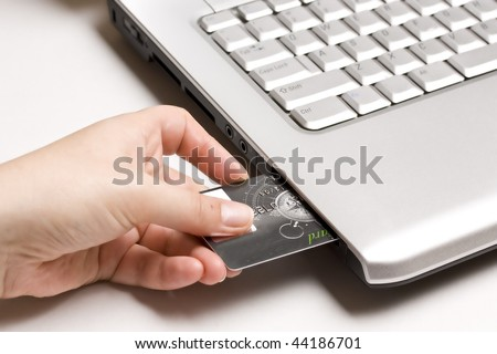 Sliding an ATM card directly into a computer - stock photo