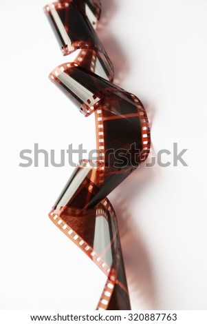 Slightly rolled camera film strip on white background - stock photo