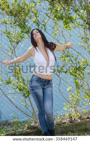 Slim athletic woman standing against fencing wire, wearing top deep decollete and jean pants - stock photo