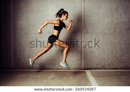 Slim attractive sportswoman running  against a concrete wall - stock photo