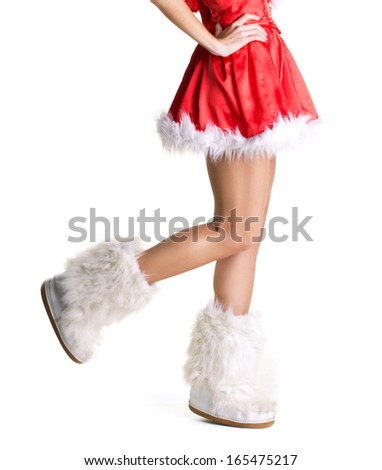slim beautiful  legs in fur boots of young woman in christmas dress on white background - stock photo