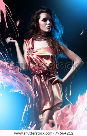 slim beautiful woman in pink dress and paint splash - stock photo