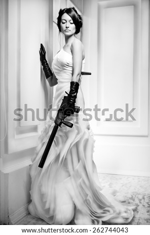 Slim beautiful woman wearing luxurious wedding dress. Bride with gun is posing against the white wall - stock photo