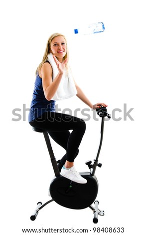 Slim blonde girl catching a bottle of mineral water or other drink while training on exercise stationary bike - stock photo