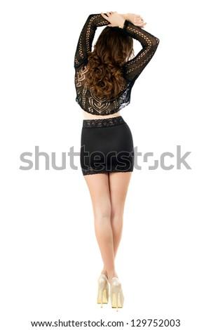 Slim brunette in black skirt and blouse posing back. Isolated on white - stock photo