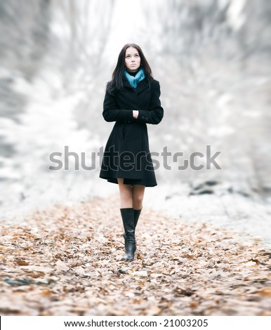 Slim brunette woman walking in a park. Special background blur effect. - stock photo