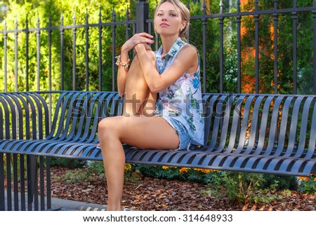 Slim caucasian girl in jeans shorts and summer tshirt sitting on iron bench. - stock photo