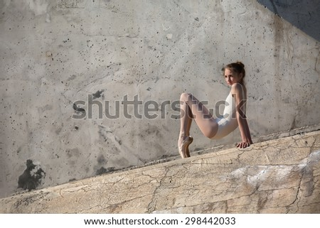 Slim dancer sits in a ballet pose - stock photo