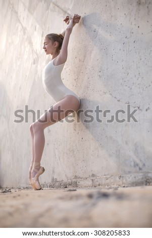 Slim dancer stands in a ballet pose - stock photo