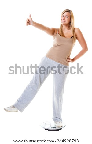 Slim down concept. Woman plus size large content girl on weight scale celebrating weightloss progress after healthy dieting, thumb up gesture - stock photo