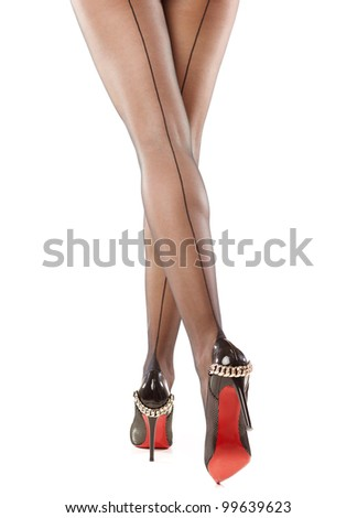 Slim female legs in dark stockings wearing high heels over isolated white - stock photo
