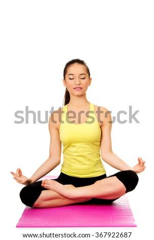 Slim female meditating in pose of lotus. - stock photo