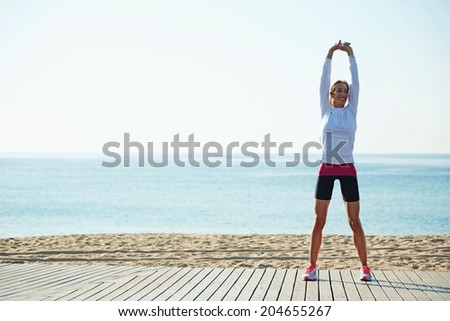 Slim female runner with beautiful figure doing stretching exercise on the beach, morning run, fitness and healthy lifestyle concept - stock photo